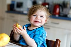 Cute adorable toddler girl eating fresh pear . Hungry happy baby child of one year holding fruit. Girl in domestic kitchen, having healthy meal snack. Smiling Royalty Free Stock Photography