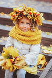 Cute adorable toddler girl portrait with bouquet of autumn leaves and wreath walking outdoor in park Stock Image