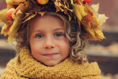 Cute adorable toddler girl portrait with bouquet of autumn leaves and wreath walking outdoor in park Stock Photos