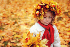 Cute adorable toddler girl portrait with bouquet of autumn leaves and wreath walking outdoor in park Stock Photography