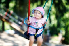Cute adorable toddler girl swinging on outdoor playground. Happy smiling baby child sitting in chain swing. Active baby. On sunny summer day outside stock image