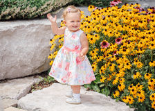 Cute adorable white Caucasian baby girl child in white dress standing among yellow flowers outside in garden park Royalty Free Stock Photography