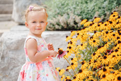Cute adorable white Caucasian baby girl child in white dress standing among yellow flowers outside in garden park looking in camer Stock Photography