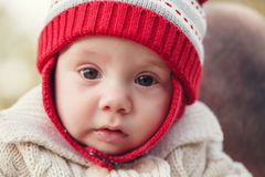 Cute adorable white Caucasian smiling baby girl boy with large brown eyes in red knitted hat. Closeup portrait of cute adorable white Caucasian smiling baby girl Stock Images