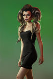 Cute adult female in black dress and creative hairstyle on green Royalty Free Stock Image