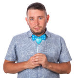 Cute adult man with a beard in a blue bow tie in summer shirt with a heart in hands Stock Images