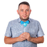 Cute adult man with a beard in a blue bow tie in summer shirt with a heart in hands on an isolated white background Royalty Free Stock Image