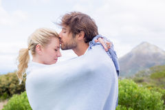 Cute affectionate couple standing outside wrapped in blanket Royalty Free Stock Photos