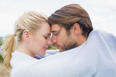 Cute affectionate couple standing outside wrapped in blanket Stock Photos
