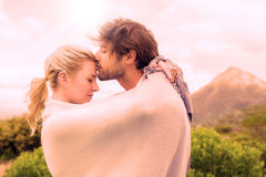 Cute affectionate couple standing outside wrapped in blanket Stock Photography