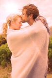 Cute affectionate couple standing outside wrapped in blanket Royalty Free Stock Image