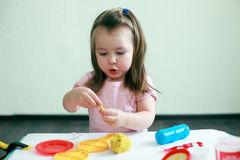 Cute affective emotional girl playing with play dought in her home. Concept of preschool education royalty free stock photography