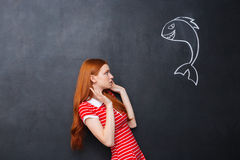 Cute afraid woman scared of shark drawn on chalkboard background Royalty Free Stock Images
