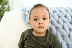Cute African-American baby in stylish clothes. On couch stock photos