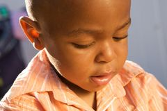 Cute African American Boy. Looking down working on something Stock Image