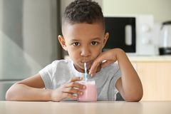 Cute African American boy drinking yogurt. At home Stock Images