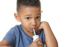 Cute African American boy drinking yogurt. On white background Stock Images