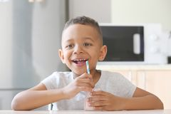 Cute African American boy drinking yogurt. At home Stock Photography