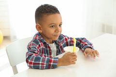 Cute African American boy eating yogurt. At home Stock Image
