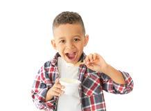 Cute African American boy eating yogurt. On light background Royalty Free Stock Photo