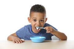 Cute African American boy eating yogurt royalty free stock photo