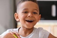 Cute African American boy eating yogurt. At home Royalty Free Stock Photo