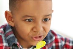 Cute African American boy eating yogurt at home. Closeup Stock Photos