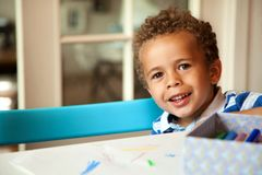 Cute African American Boy Smiling Looking at You. Smiling African American boy sitting on a chair and getting ready for his lesson Stock Photography