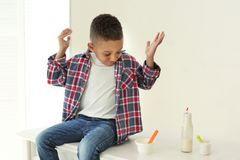 Cute African American boy with yogurt. At home Royalty Free Stock Images