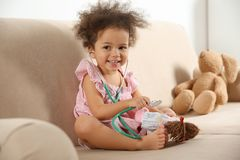 Free Cute African American Child Imagining Herself As Doctor While Playing With Stethoscope And Doll On Couch Stock Photography - 138747662