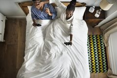 Cute African American couple on bed playing video games Stock Image