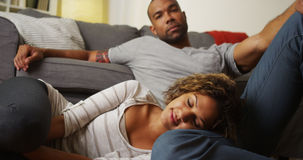 Cute African American couple sitting on floor. Looking at camera stock photo