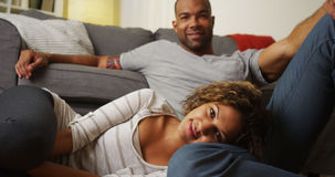 Cute African American couple sitting on floor looking at camera. At home royalty free stock images