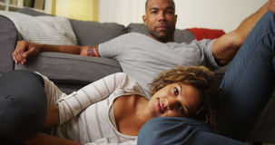 Cute African American couple sitting on floor looking at camera. At home royalty free stock photography