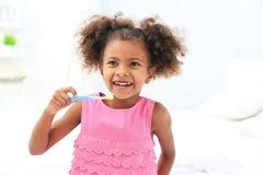 Cute African American girl brushing teeth in bathroom stock photography