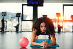 Cute african-american girl doing exercise on a yoga mat Royalty Free Stock Image