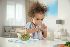Cute African-American girl with glass of water and vegetable salad at table. In living room royalty free stock images