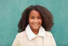 Happy African American girl with afro hair on a green background. Cute African American girl smiling with afro hair on a green background royalty free stock photos