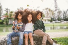 Cute african american little boy and girl hug each other in summer sunny day stock photos