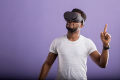 Man wearing virtual reality headset. Cute african american man in VR glasses, playing video games with virtual reality headset, interacting with invisible screen royalty free stock photography
