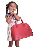 Cute african american small girl dressed up as an adult woman wi. Th coloful necklaces and a huge red handbag - isolated on white Stock Image