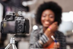 Cute african american woman with curly hair conducting fashion tutorial. Fashion tutorial. Cute african american woman with curly hair showing new colors while royalty free stock photography