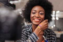 Cute african american woman with curly hair showing new colors stock photos