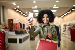 Cute african american woman taking selfie with shopping bags and smiling near clothing store. Black pretty girl taking. Photo or talking on video call chat Stock Image