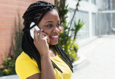 Cute african american woman in a yellow shirt listening at mobile phone Stock Photo