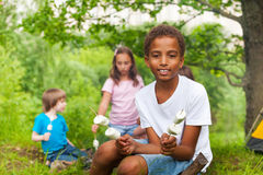 Cute African boy with marshmallows during camping Royalty Free Stock Photos