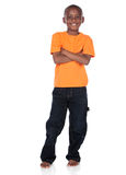 Cute african boy. Wearing a bright orange t-shirt and dark denim jeans. The boy is standing and smiling at the camera stock photo
