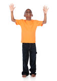 Cute african boy. Wearing a bright orange t-shirt and dark denim jeans. The boy is worshipping with his hands lifted up Royalty Free Stock Photos