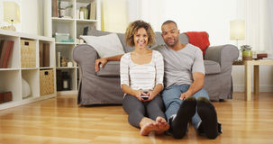 Cute African couple sitting on floor in living room Royalty Free Stock Photo