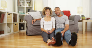 Cute African couple sitting on floor in living room Stock Image